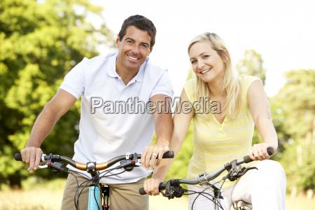 andare in bicicletta coppia in campagna